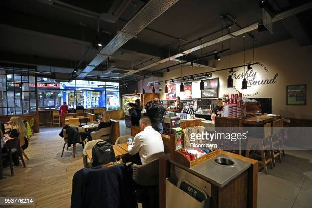 Customer sit at tables inside a Costa Coffee shop operated by Whitbread Plc in London UK on Wednesday May 2 2018 Whitbread is betting that its...