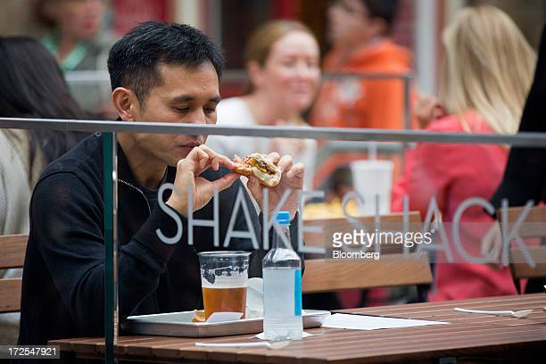 A customer sits and eats a cheeseburger outside Shake Shack's new burger restaurant in London UK on Tuesday July 2 2013 Shake Shack opening in...