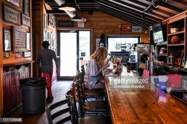 A customer sits at the bar as she eats at Moe's Original BBQ restaurant amid the coronavirus pandemic in Atlanta Georgia on April 27 2020 Some...