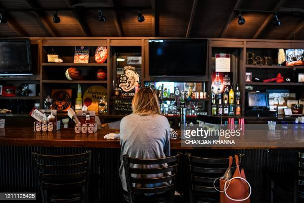 A customer sits at the bar as she eats in Moe's Original BBQ restaurant amid the coronavirus pandemic in Atlanta Georgia on April 27 2020 Some...