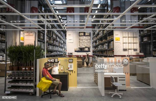A customer sits beside a room display after shopping on the opening day of IKEA of Sweden AB's first department store in Belgrade Serbia on Thursday...