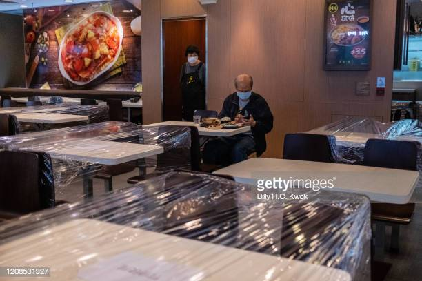 A customer sits in a restaurant with taped off seatings to make sure people adhere to social distancing during a coronavirus on March 29 2020 in Hong...