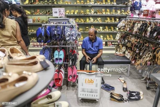 A customer sits next to a display of footwear at a Big Bazaar hypermarket operated by Future Retail Ltd in Mumbai India on Sunday April 16 2017...