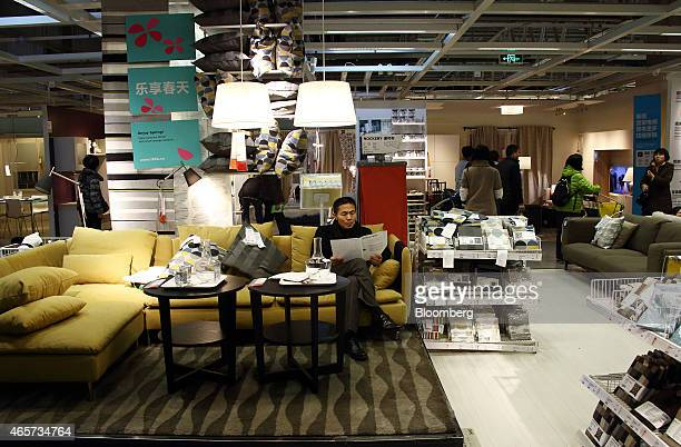 A customer sits on a couch while reading a pamphlet inside the Ikea Beijing Xihongmen Store operated by Ikea AB in Beijing China on Monday March 9...