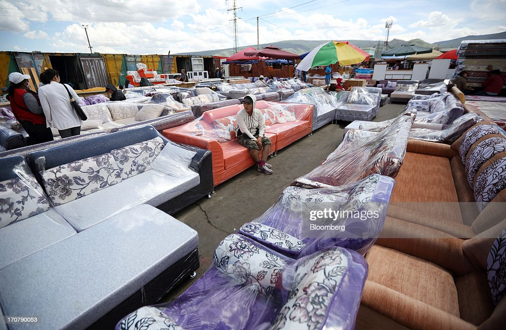 A customer sits on a sofa displayed for sale at a market in Ulaanbaatar, Mongolia, on Thursday, June 13, 2013. Mongolia, a country of almost 2.9 million people, is experiencing double-digit growth and new opportunities in the mining industry. Photographer: Tomohiro Ohsumi/Bloomberg via Getty Images