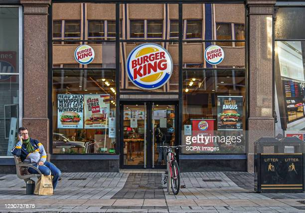Customer sits outside Burger King fast food store.