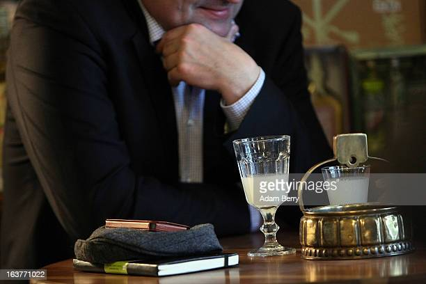 A customer sits with a glass of absinthe at the Absinth Depot shop on March 15 2013 in Berlin Germany The highly alcoholic drink absinthe was banned...
