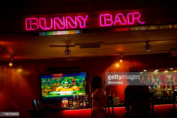 A customer sits with an employee inside the bar area of the Moonlite Bunny Ranch in Mound House Nevada US on Tuesday Aug 20 2013 Growing use of the...
