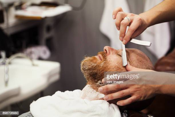 A customer sitting in the barbers chair, having a wet shave by a barber using a cut throat razor.