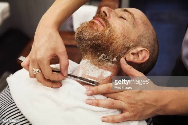 A customer sitting in the barbers chair, having his chin shaved by a barber using a cut throat razor.