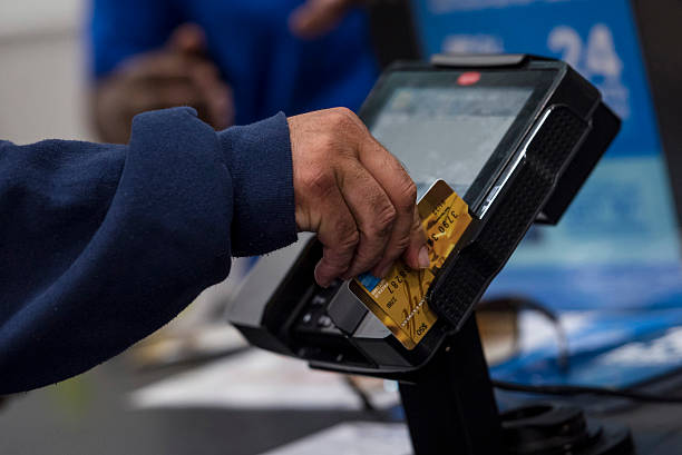 Inside a best buy co store ahead of earnings figures photos and a customer slides a pre paid american express credit card through a card reader at reheart Gallery