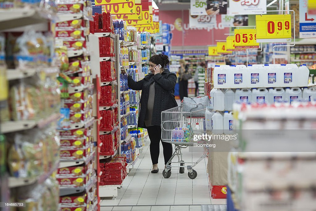 A customer speaks on a mobile handset while selecting goods in the aisle of a Carrefour SA supermarket at the Mall of Cyprus in Nicosia, Cyprus, on Tuesday, March 26, 2013. Controls on capital movements to prevent money from draining out of the banking system -- allowed in exceptional circumstances under European Union law -- will remain for 'a matter of weeks,' Cypriot Finance Minister Michael Sarris said. Photographer: Simon Dawson/Bloomberg via Getty Images