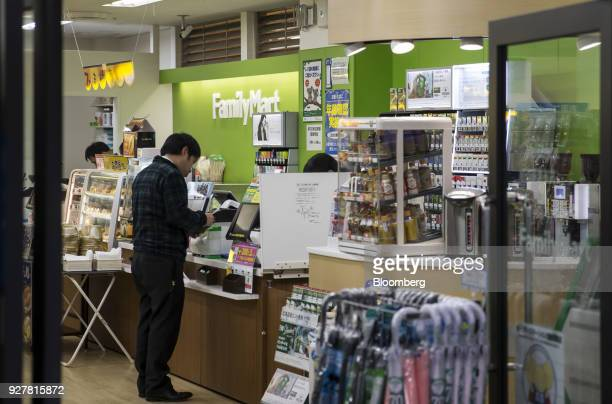 A customer stands at a checkout counter inside a FamilyMart UNY Holdings Co FamilyMart convenience store in Tokyo Japan on Friday Feb 23 2018...