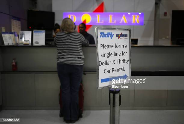 A customer stands at a Dollar Thrifty Automotive Group Inc rental counter inside Indianapolis International Airport in Indianapolis Indiana US on...