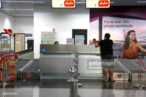 A customer stands at an AirAsia Bhd checkin counter at the UTapao International Airport in Ban Chang district Rayong Province Thailand on Tuesday...