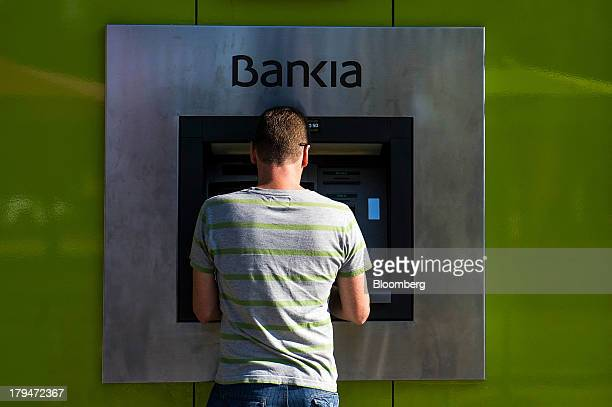 A customer stands at an automated teller machine outside a Bankia SA bank branch in Tarragona Spain on Wednesday Sept 4 2013 Bankia is set to agree...