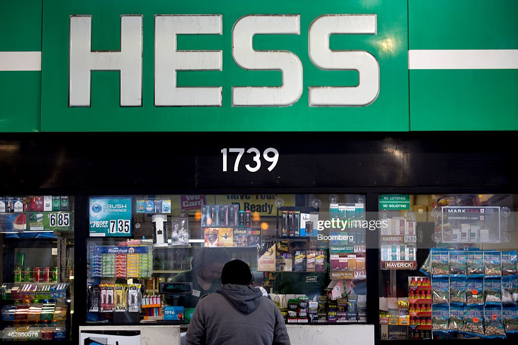 A customer stands below a Hess Corp. sign at a gas station in Washington, D.C., U.S., on Monday, Jan. 26, 2015. Hess Corp. is expected to report fourth-quarter earnings figures on Jan. 28. Photographer: Andrew Harrer/Bloomberg via Getty Images