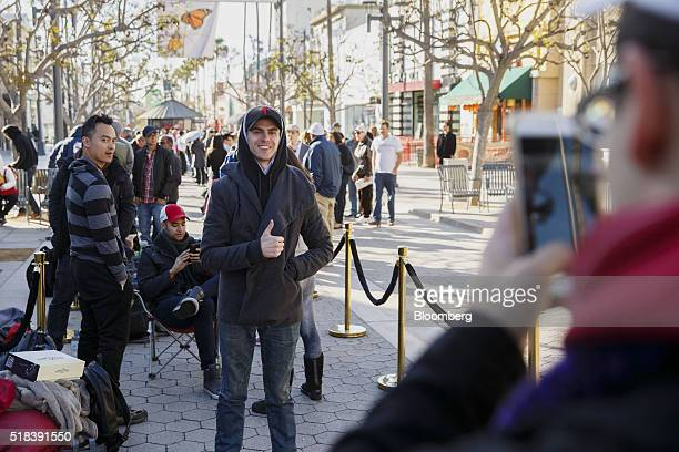 A customer stands for a photograph while waiting in line ahead of the Model 3 announcement outside the Tesla Motors Inc store on the Third Street...