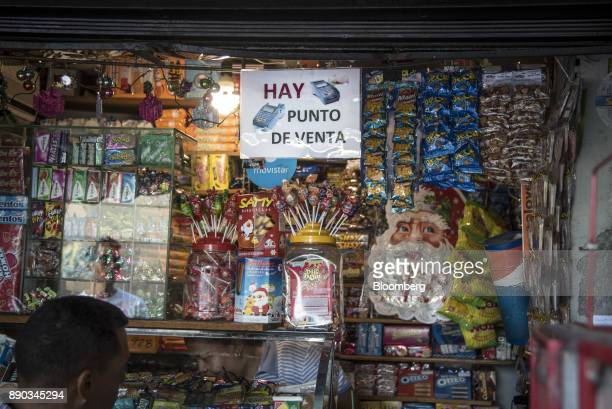 A customer stands in front of a sign indicating that credit cards are accepted at a newsstand in the Chacao district of Caracas Venezuela on...