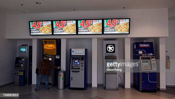 A customer stands in front of automated teller machines for from left National Bank of Greece Piraeus Bank SA Emporiki Bank SA Alpha Bank AE and...