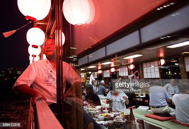 A customer stands on the deck of a yakatabune or traditional low barge style boat operated by Mikawaya shipping agent as it sails through Tokyo Bay...