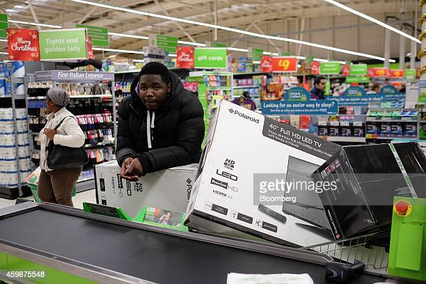 A customer stands with shopping carts laden with boxed electronic goods including LED televisions as he waits at a checkout desk during a Black...