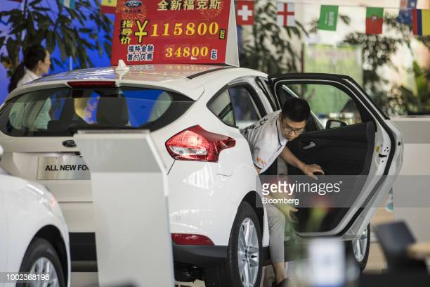 A customer steps out of a Ford Motor Co vehicle on display at a Ford dealership in Shanghai China on Thursday July 19 2018 The fledgling USChina...