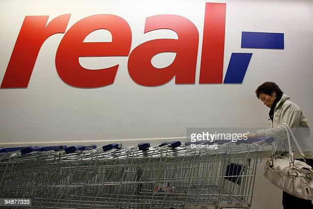 A customer takes a grocery cart at a Metro AGowned Real store in Berlin Germany on Monday March 17 2008 Metro AG Germany's largest retailer reported...