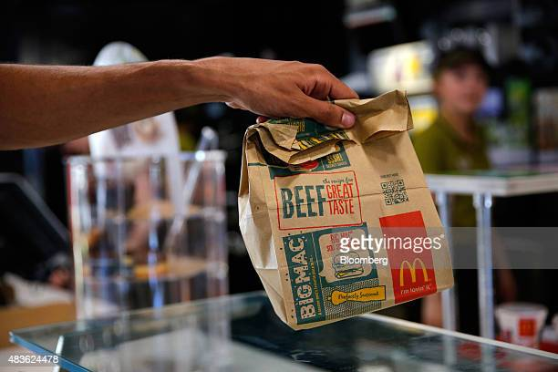 A customer takes a McDonald's Corp bag of food inside a McDonald's restaurant in Manchester UK on Monday Aug 10 2015 McDonald's Chief Executive...