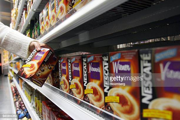 A customer takes a package of Nescafe produced by Nestle from a shelf at a grocery store in Zurich Switzerland on Thursday Oct 18 2007 Nestle SA the...