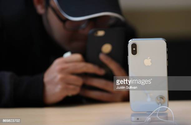 A customer takes a picture of the new iPhone X at an Apple Store on November 3 2017 in Palo Alto California The highly anticipated iPhone X went on...