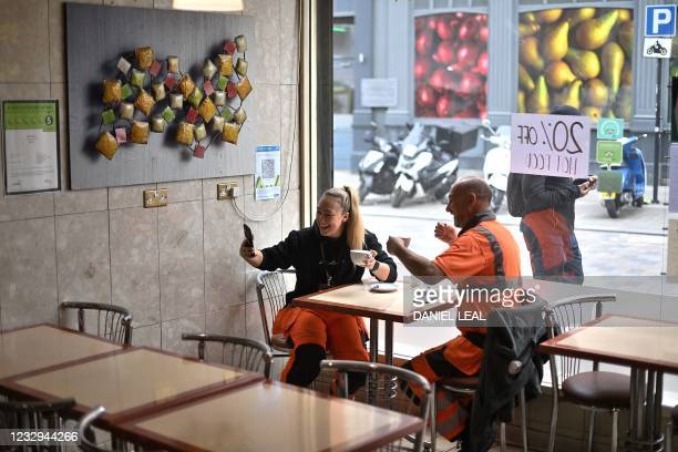 Customer takes a selfie photogrpah as she sits at a table inside Barbarella's cafe in London as Covid-19 lockdown restrictions ease across the...