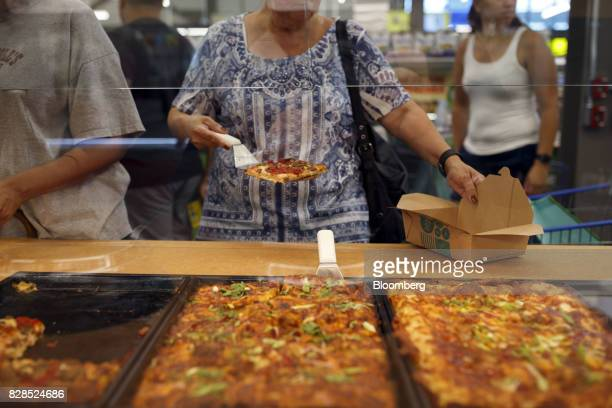 A customer takes a slice of pizza during the grand opening of a Whole Foods Market 365 location in Santa Monica California US on Wednesday Aug 9 2017...