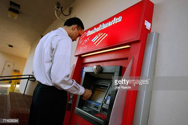 A customer takes money out of a Bank of America ATM machine October 18 2007 in Miami Florida Bank of America reported that their profits plummeted 32...