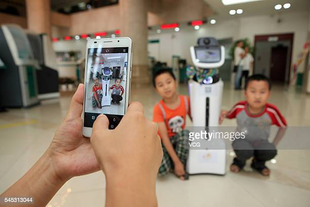 A customer takes photos as two children pose with an intelligent robot at hall of Sichuan Neijiang Branch Agriculture Bank of China on July 7 2016 in...