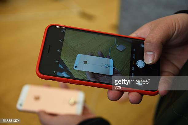 A customer takes pictures of a rose gold iPhone SE with his phone at an Apple Store on March 31 2016 in Hangzhou Zhejiang Province of China Apple...
