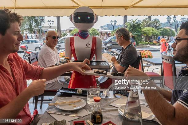 Customer takes the dish brought by the robot waiter on July 25 2019 in Rapallo Italy The Gran Caffè Rapallo restaurant in Liguria is the first...
