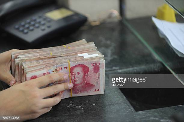 A customer takes Yuan banknotes on the counter at a branch of Bank of China in Hefei Anhui province October 14 2010 VCP