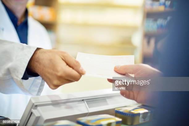kunden nehmen rechnung vom männlichen apotheker im store - verschreibungspflichtiges medikament stock-fotos und bilder