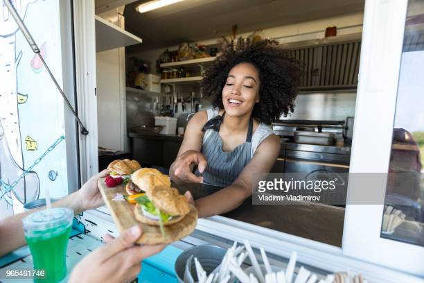 customer taking burgers from food van - food truck stock pictures, royalty-free photos & images