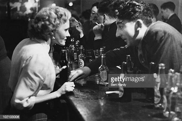 A customer talks intently to a barmaid at the Shakespeare Theatre Liverpool December 1954 Original Publication Picture Post 7450 A Grand Old Music...