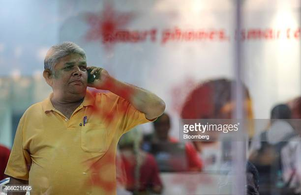 A customer talks on a mobile phone in a Bharti Airtel Ltd retail store in Mumbai India on Wednesday Jan 29 2014 The auction of wireless spectrum...