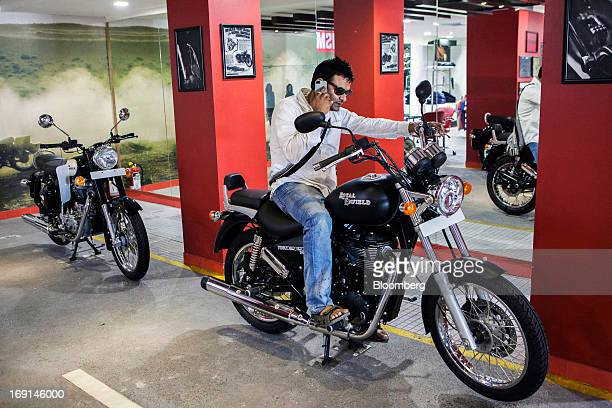 Customer talks on his mobile phone as he sits on an Eicher Motors Ltd. Royal Enfield Thunderbird 500 motorcycle on display at the company's Royal...