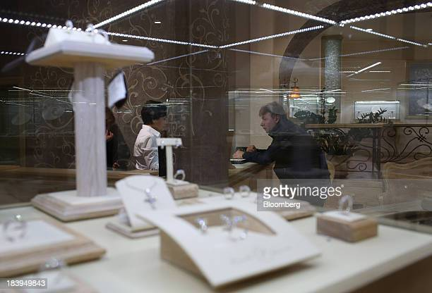 A customer talks to an employee beyond a display of diamond jewelry inside a luxury store operated by Kristall Production Corp in Moscow Russia on...