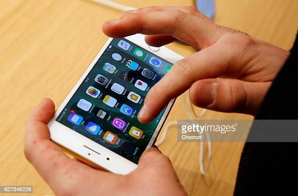 A customer touches the screen of an iPhone 7 inside the new Apple store SaintGermain during the first opening day on December 03 2016 in Paris France...