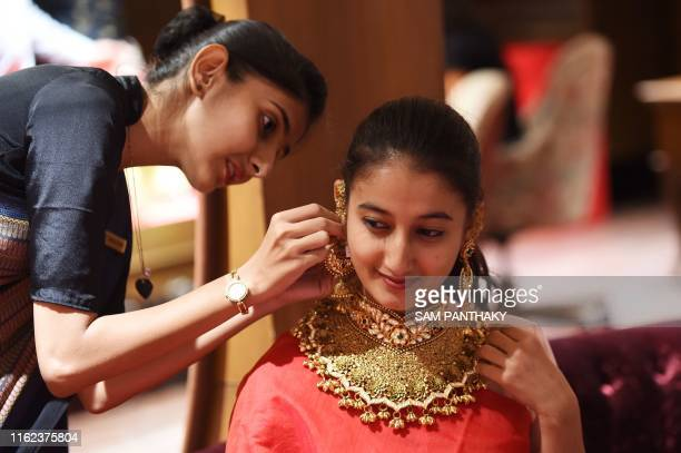 A customer tries a of 22 carat gold necklace at a jewelry shop in Ahmedabad on August 18 2019 Gold prices in India has shot surged closer to record...
