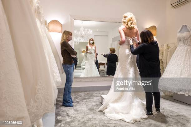 A customer tries a wedding dress in the atelier of designer Mariella Gennarino of Catania open again to the public after the lockdown on May 6 2020...