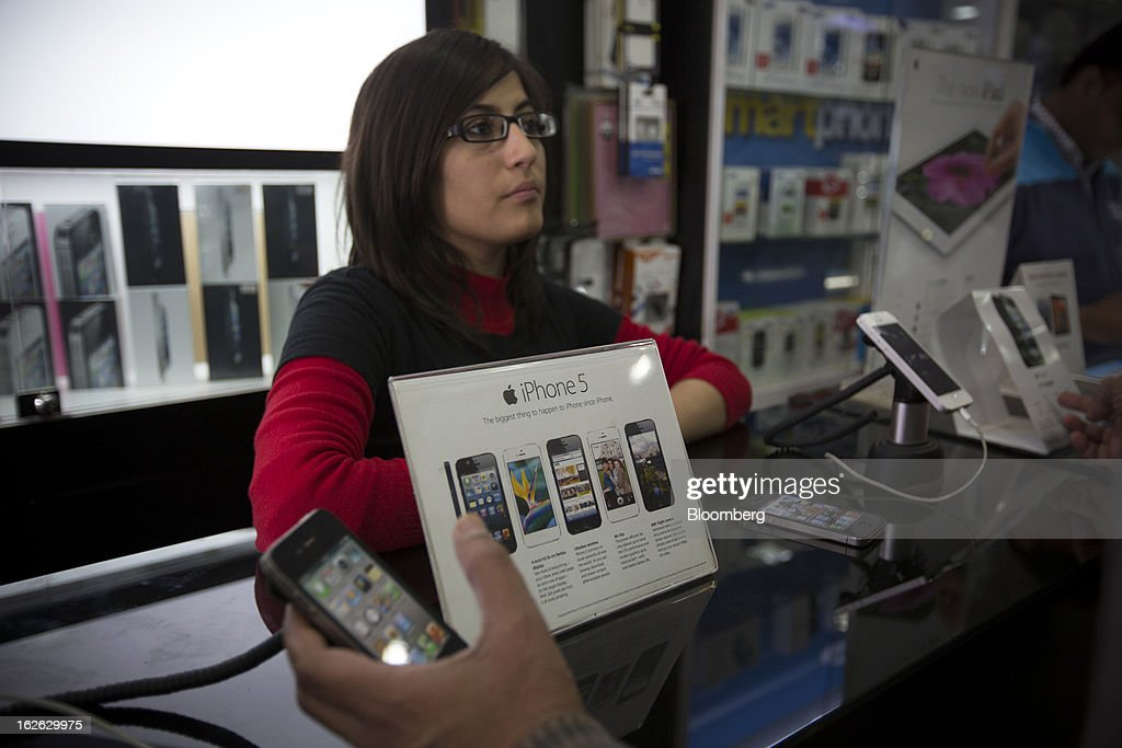 A customer tries an Apple Inc. iPhone 5 at a store in Connaught Place in New Delhi, India, on Saturday, Feb. 23, 2013. Finance Minister Palaniappan Chidambaram, who will present his annual budget to parliament on Feb. 28, will seek to narrow the shortfall to 4.8 percent of gross domestic product in the year starting April, from this year's goal of 5.3 percent, according to a Bloomberg survey of analysts and investors. Photographer: Brent Lewin/Bloomberg via Getty Images