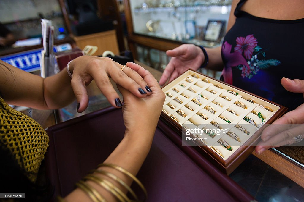 A customer tries on a gold ring at the counter of a jewelry store in Lisbon, Portugal, on Wednesday, Aug. 22, 2012. In Portugal, the historical home of some of Europe's biggest gold reserves, the number of jewelry stores, which include cash-for-gold shops, increased 29 percent in 2011 from a year earlier, a study commissioned by parliament found. Photographer: Mario Proenca/Bloomberg via Getty Images