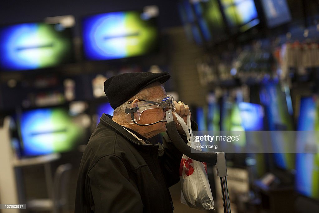 A customer tries on a pair of 3-D glasses in the television department of a Sears Holdings Corp. store in Jersey City, New Jersey, U.S., on Tuesday, Jan. 24, 2012. The U.S Census Bureau is scheduled to release durable goods data on Jan. 26. Photographer: Victor J. Blue/Bloomberg via Getty Images